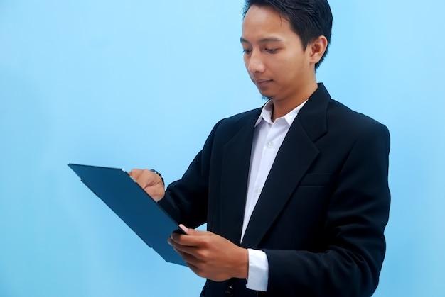 彼のタブを通して彼のビジネスの発展を見ている若いビジネスマンの肖像画
