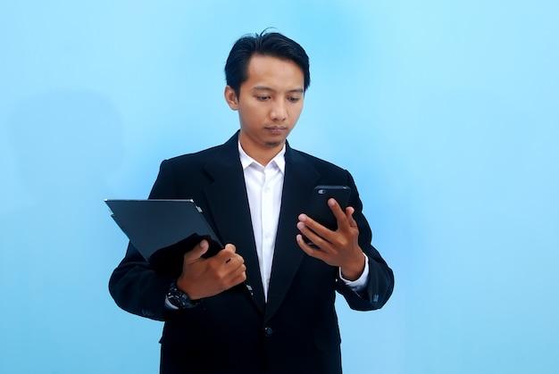 Портрет молодого бизнесмена, смотрящего на развитие своего бизнеса через вкладки и смартфоны