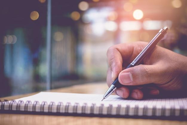 男性のクローズアップは、図書館で宿題の教科書を書くペンを手します。教育の概念