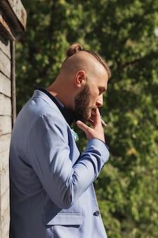 タバコを吸っている間、カメラから離れている流行に敏感な若い男