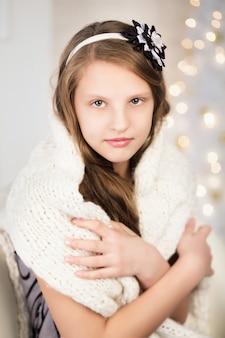 暖かいニットセーターに包まれたかなり笑顔の十代の少女の肖像画