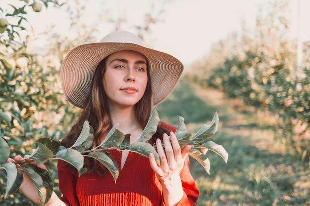 Портрет в саду. молодая и красивая женщина в шляпе и красном платье, с веткой дерева в руках