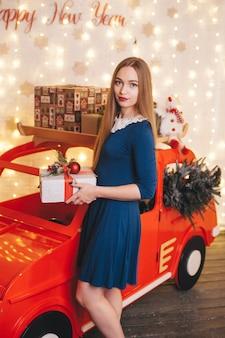 クリスマスのインテリアで車の中で美しい女性。