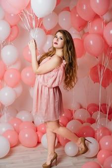 Красивая молодая девушка в платье среди много розовых шаров.