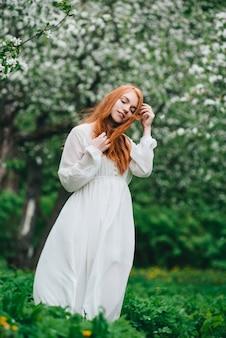 Красивая рыжеволосая девушка в белом платье среди цветущих яблонь в саду.