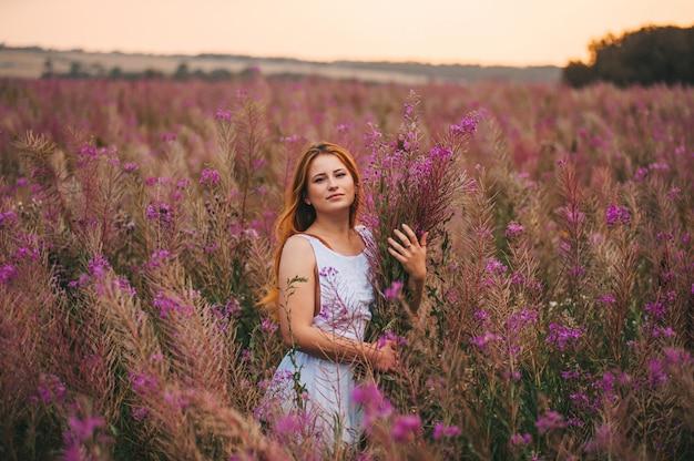 柳茶の開花フィールドでドレスを着た美しい赤い髪の少女。