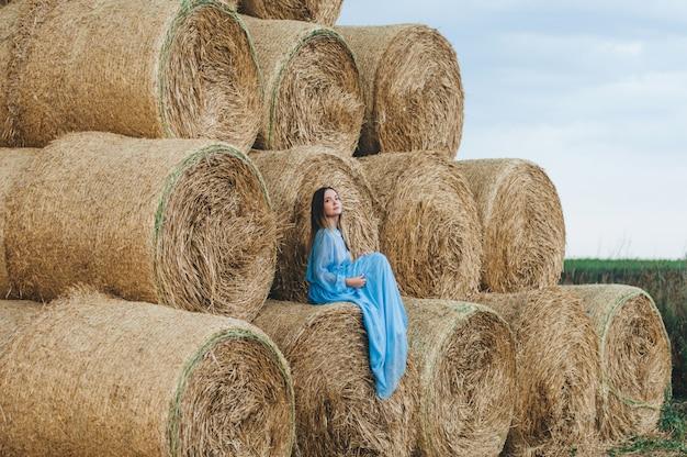 干し草の山のドレスを着た美しい女性。