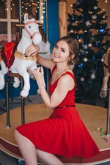 美しい若い女性は馬とカルーセルの近くで喜ぶ。クリスマス。