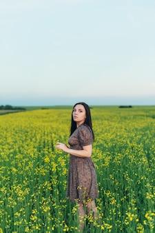 フィールドで夕暮れ時の美しい若い女性