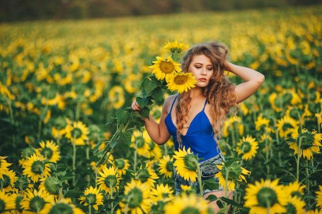 咲くひまわりの中でドレスを着た若い美しい女性。農業文化。