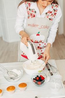 カップケーキのクリームを作る若い女の子。
