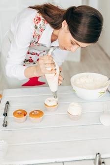 若い女の子がクリームでカップケーキを飾ります。