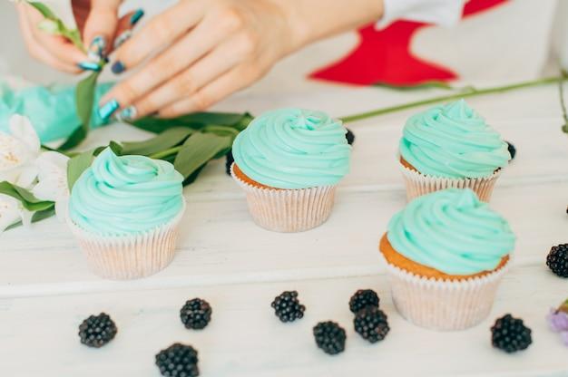 若い女の子が新鮮なベリーと花でカップケーキを飾る