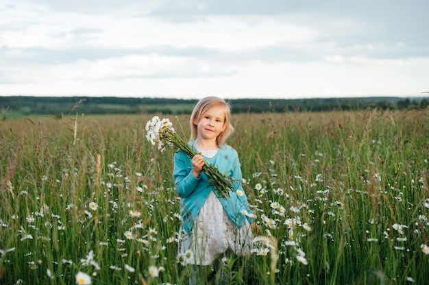 Маленькая девочка в ромашковом поле