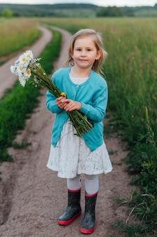 Ребенок на дорожке с букетом ромашек в сапогах