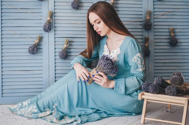青い壁にラベンダーと座っている美しい若い女性。