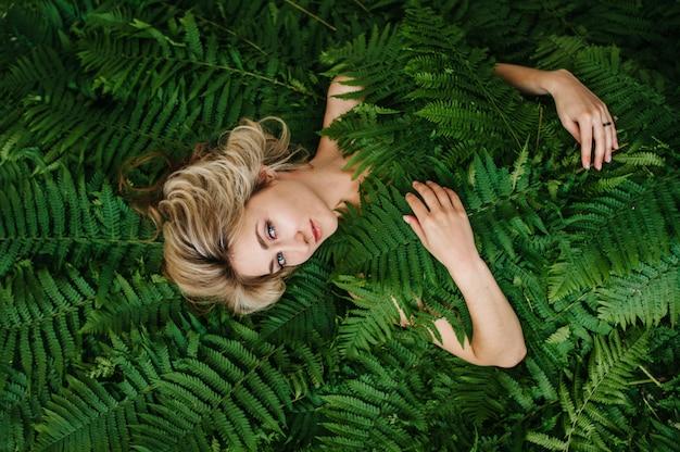 Красивая девушка лежит в папоротнике.