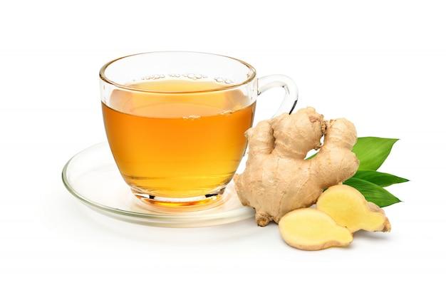 Стеклянная чашка горячего имбирного чая с нарезанным корневищем имбиря на белом фоне