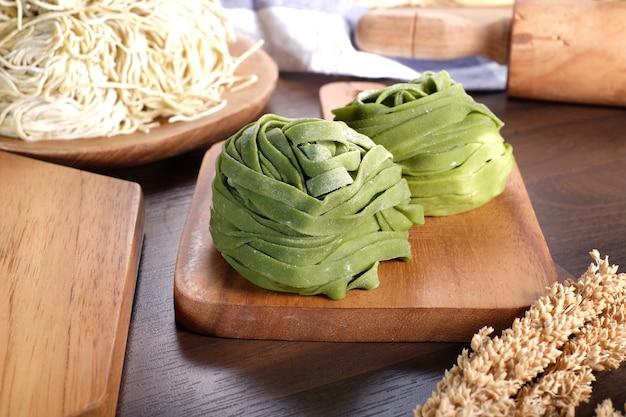 木の板に緑の生麺