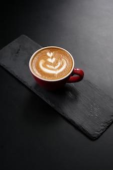 赤いマグカップにアートとカプチーノコーヒー