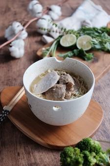お箸でボウルにミートボールとおいしい上品な黄色の麺