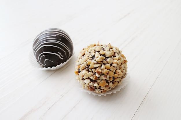 ショコラテとピーナッツ、白い木製のテーブルの甘いミニケーキ