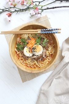箸と木製のボウルに卵と牛肉のおいしい熱いラーメン
