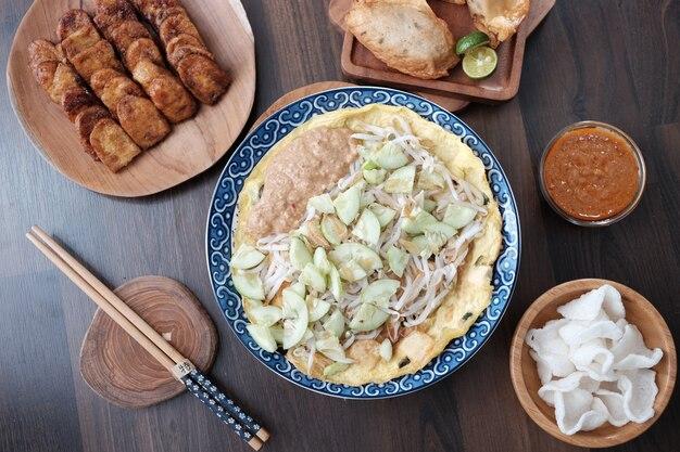 Популярная индонезийская еда лотек с палочками для крекеров из говядины и соусом чили на коричневом деревянном столе