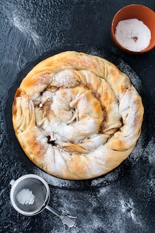 Круглый бурековый пирог с яблоком на темном фоне. традиционная сербская кухня. выборочный фокус. вид сверху.