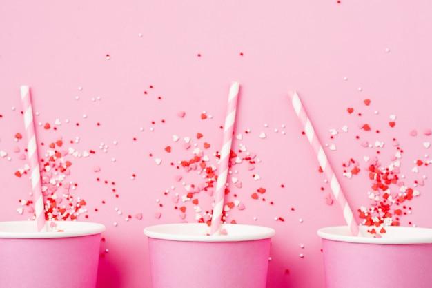 Три розовый бумажный стаканчик кофе на розовом фоне бумаги света. ноль отходов концепции. квартира лежала.
