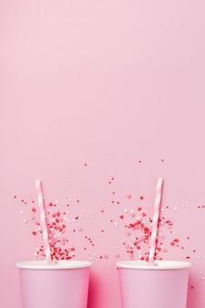 Две розовые бумажный стаканчик кофе на розовом фоне бумаги света. ноль отходов концепции. квартира лежала.