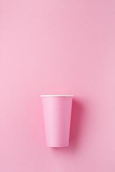 Один розовый бумажный стаканчик кофе на розовом фоне бумаги света. ноль отходов концепции. квартира лежала.