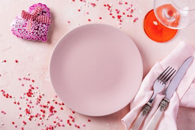 ピンクの明るい背景にピンクのプレートとギフトの心とバレンタインデーのテーブルの設定