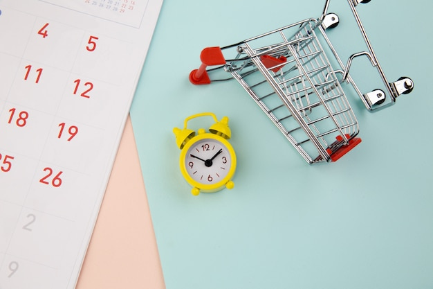 黄色の目覚まし時計、ショッピングオンラインコンセプトのトロリー