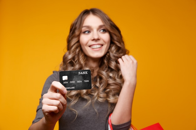 買い物袋を押しながらクレジットカードを示す驚いて幸せな少女の肖像画