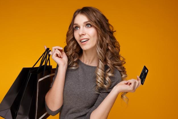 クレジットカードと買い物袋を保持している幸せな若いブルネットの女性の肖像画