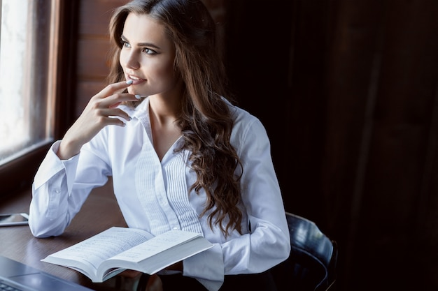Молодая женщина, работающая с ноутбуком и документами. красивая женская книга чтения около окна.