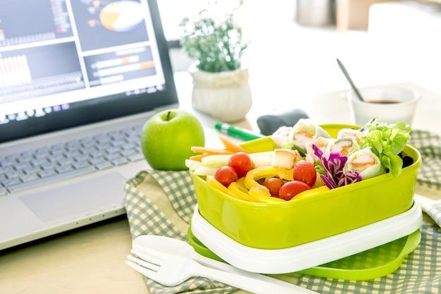 Закройте зеленый обеденный ящик на рабочем месте рабочего стола