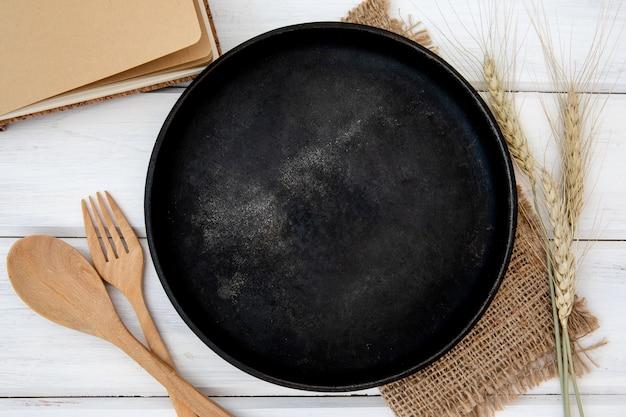 Черная металлическая тарелка и скатерть с деревянной вилкой и ложкой на столе