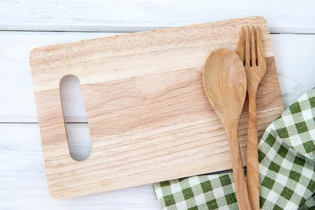 Рубящая разделочная доска и скатерть с деревянной вилкой и ложкой на белом столе