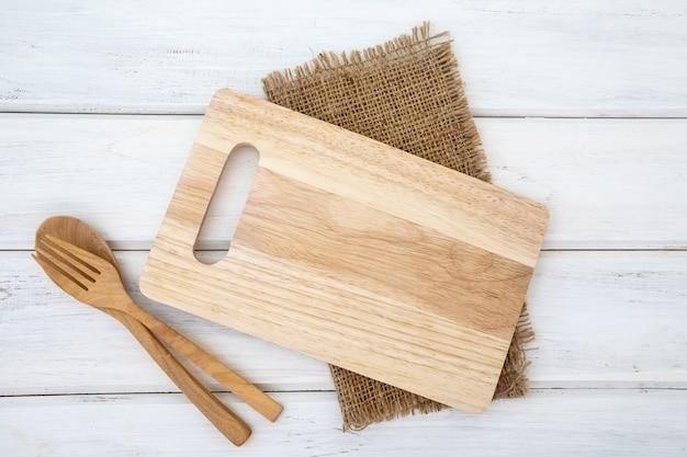 Разделочная доска и скатерть с деревянной вилкой и ложкой на белом столе