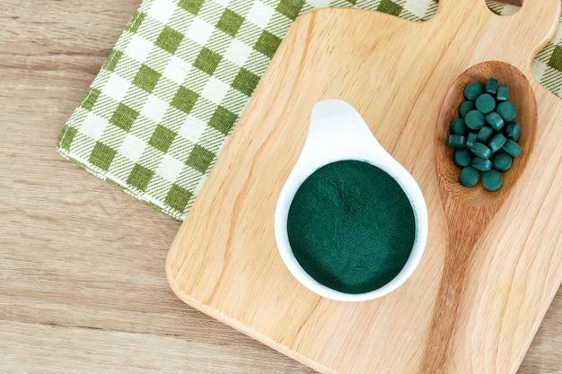 ボウルにスピルリナパウダー、スプーン、健康的なスーパーフードダイエット、デトックス栄養概念のスピルリナ薬を閉じる