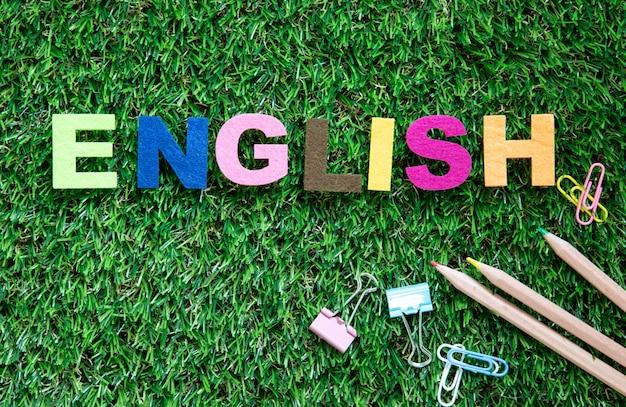 緑の芝生の庭の背景にカラフルな英語単語キューブ