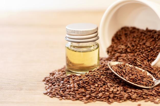 Закройте вверх по эфирному маслу льняного семени и семенам в деревянной ложке