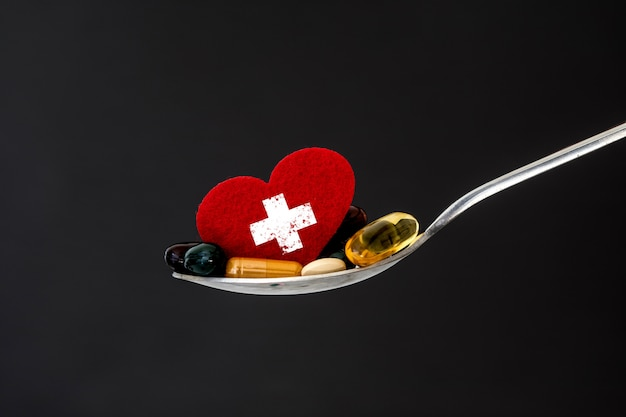 スプーンで赤いハートとカラフルな医療サプリメントと薬の丸薬