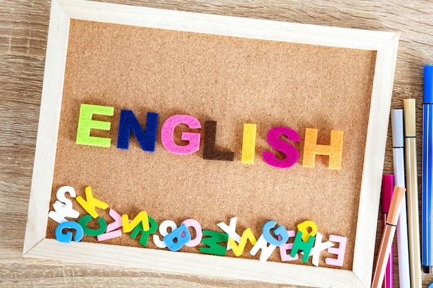 ピンボードの背景にカラフルな英語単語のアルファベット