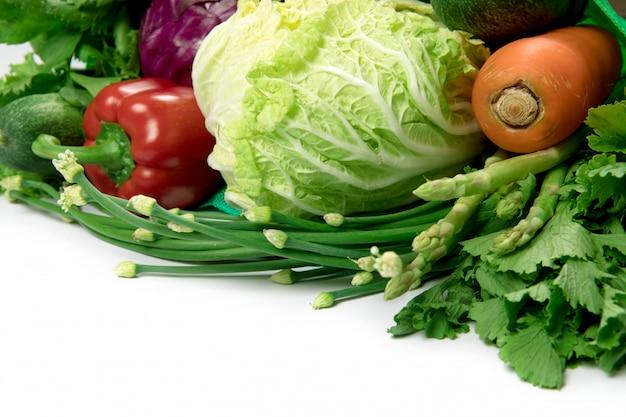 Закройте зеленый продуктовый мешок из смешанных органических зеленых овощей на белом