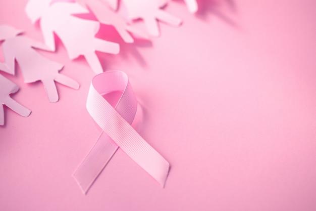 乳がんの意識のためのピンクの背景の女の子の紙人形と甘いピンクのリボンの形