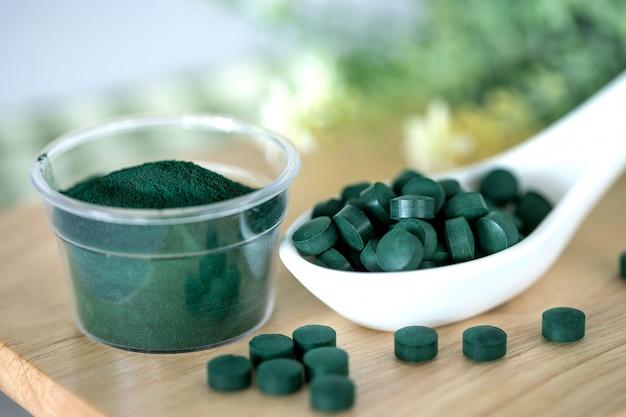 スプーン、健康的なスーパーフードダイエット、デトックス栄養でスピルリナパウダーとスピルリナの丸薬を閉じる