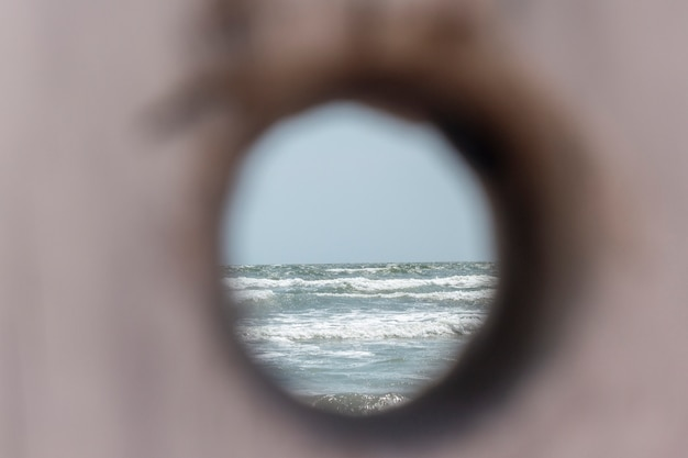 彫刻された木の幹を通って見られる波の海;海辺で